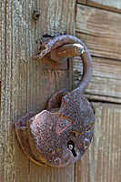 Detail of an open padlock hanging on a bolt
