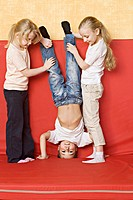 Two girls holding a boy upside down