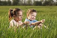 Two young girls sitting in a field
