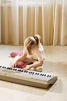 A girl playing an electronic keyboard