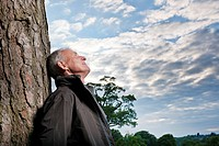 Man leaning against tree outdoors