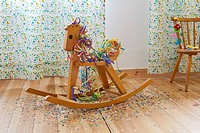 A rocking horse amongst streamers, confetti and happy birthday banner