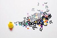 A toy Easter chick next to a group of musical notes and confetti (thumbnail)