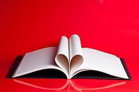 An open hardcover book with pages folded to look like a heart