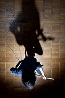 Guitarist sitting on stage in spotlight (thumbnail)
