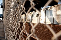Train seen through wire fence which separates the pedestrian walkway on Manhattan Bridge