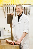 Butcher holding large knife and meat