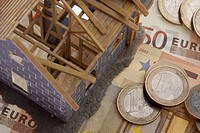 A partially constructed miniature model of a house standing on top of European Union currency