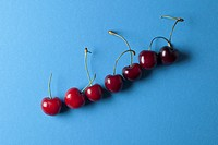A row of ascending cherries with stems