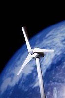A model of a wind turbine in front of the planet earth