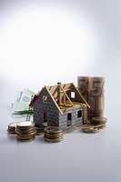 A partially constructed house with European Union currency and coins around it