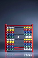 An abacus with neat rows of multi colored beads and a single white bead in the middle (thumbnail)