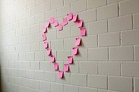 Blank adhesive notes arranged into the shape of a heart on a brick wall
