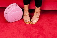 A woman wearing gold strappy heels focus on feet next to a pink purse