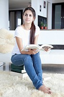 Woman sitting on books and reading (thumbnail)