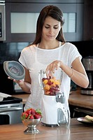 Woman putting fruit into blender
