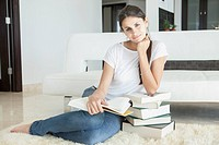 Woman at home leaning on books reading (thumbnail)