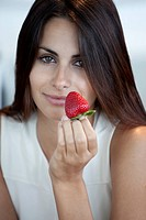 Elegant woman offering strawberry