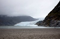 A distant person standing on a beach near Mendenhall Glacier, Alaska