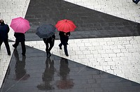 Pedestrians below with umbrellas