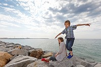 Children playing on rocks at beach