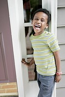 A cheerful laughing boy standing at the front door of his house