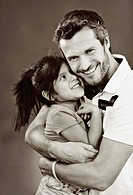 A man embracing his young daughter, studio shot