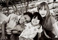 Three cheerful kids in a backyard
