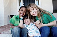 Three kids laughing affectionately while sitting on the front stoop