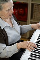 A senior woman playing an upright piano
