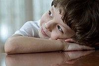 A young boy resting his head on his clasped hands, looking up and away