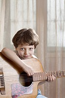 A young boy holding an acoustic guitar