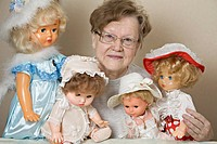 A senior woman with her collection of old_fashioned dolls