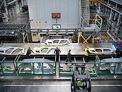 High angle view of workers handling car parts as they come out of press in car factory