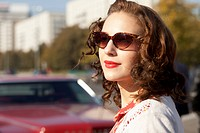 A pretty rockabilly woman standing near a vintage care, focus on woman
