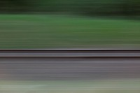 Railroad tracks and grass seen in blurred abstract pattern from moving train