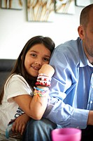 Girl hugging fathers arm on sofa