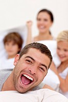 Portrait of laughing father playing with family in bed
