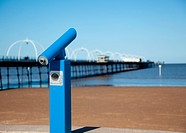 Blue telescope by blurred Southport pier