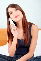 Pretty woman with phone sitting on bed