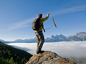 Canada, Alberta, Banff National Park, Climber throwing rope from rock summit above clouds