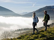 Italy, Piedmont, Couple looking at mountains from meadow above fog