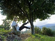 Italy, Liguria, Woman relaxing on bench below olive tree