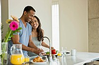 Couple making breakfast in loft apartment
