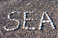 word sea made of white stones on a background of a coastal pebble