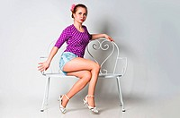 Pin up girl sitting on bench and looking