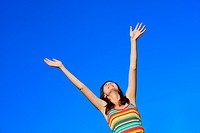 A young happy woman with hands up against blue sky