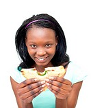 Joyful young woman eating a sandwich