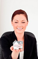 Good looking red_haired woman in suit holding a miniature house