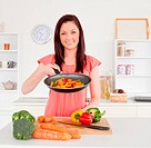 Gorgeous red_haired woman cooking vegetables in the kitchen